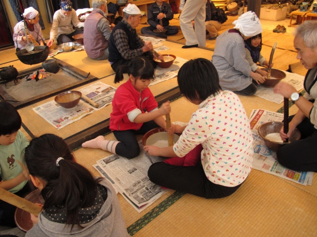 米をすりつぶしてカラコを作る参加者